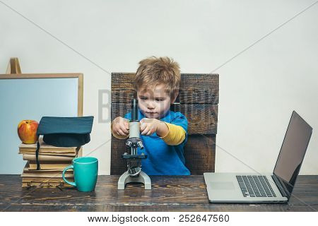 Science. Biology. Experiment. Education. Study. Thoughtful smart boy working with microscope and laptop. Little kid in graduation hat with microscope. Modern technology. stock photo