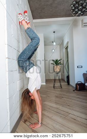 A woman is standing on his hands upside down stock photo