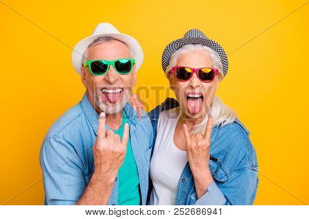 My parents are crazy Music lovers rock fans concept youth concept. Close up photo portrait of excited funky funny comic cheerful guy and lady making stick tongue out sign isolated bright background stock photo