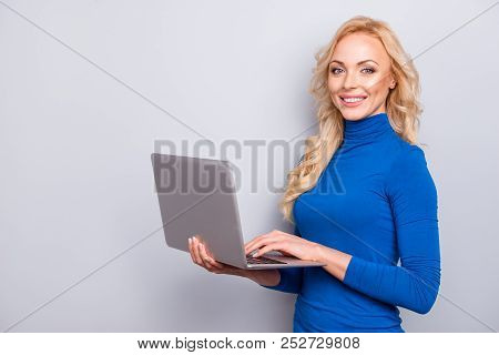 Portrait with copy space, empty place of pretty, trendy, charming, sexy, cute,  woman in blue turtleneck, looking at camera isolated on grey background, having laptop in hands, using wi-fi internet stock photo