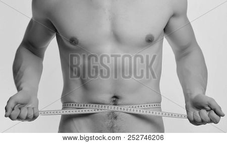 Athlete with strong muscles measures waist or sixpacks. Guy with nude chest on white background. Man with tape stock photo