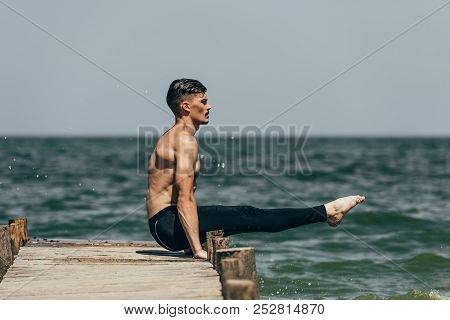 handsome shirtless man practicing yoga and doing arm balance on pier stock photo