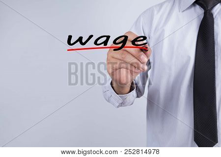 Businessman hand writing Wage with red marker on transparent wipe board, business concept. stock photo