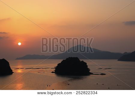 Early morning sunrise casting a warm glow over silhouetted islands in the Pacific Ocean off Toba, Japan, with fishery rafts visible in the water. stock photo