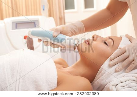 Cosmetologist using electronic tool for professional facial stock photo