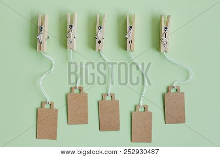 Blank brown cardboard price tags, sale tag, gift tag, address label, luggage label hanging on clothes wooden clips on pastel green background. Mock up, copy space for text, top view stock photo