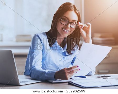 Young Pretty Lady Reading Documents And Smiling While Working In Office. Accountant Manager. Office
