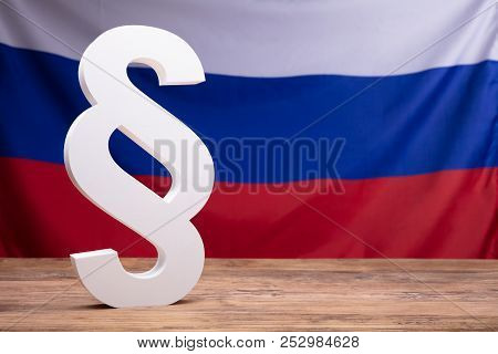 Close-up Of White Paragraph Symbol On Wooden Desk In Front Of Russian Flag stock photo