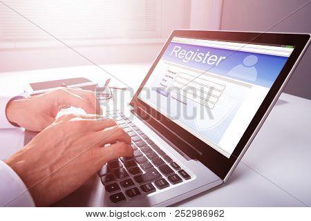 Businessman's Hand Filling Online Registration Form On Laptop stock photo