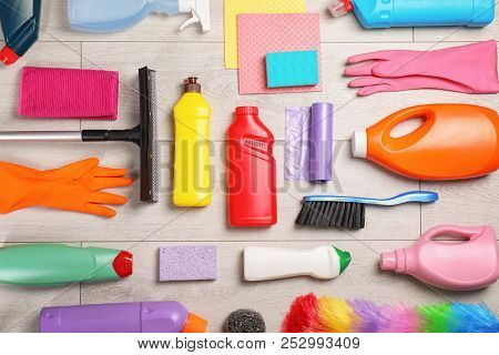 Flat lay composition with cleaning supplies on wooden background stock photo
