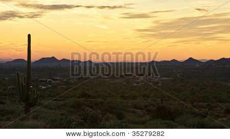 The sun sets over Apache Mesa and Phoenix AZ stock photo