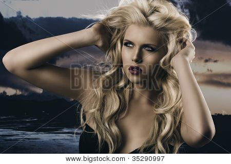portrait of young sexy girl with blode wavy hairstyle and and flying hair from wind she is turned of three quarters at right and her hands are on the head in the hair stock photo