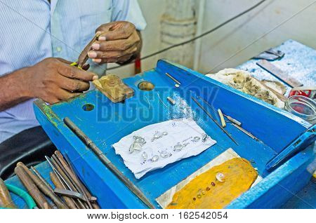 The jeweler's workplace with the pieces of siver wire and faceted moonstones Meetiyagoda Sri Lanka. stock photo