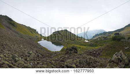 Beautiful mountain lake surrounded by impressive mountains of the Khamar-Daban. Panorama with high resolution. stock photo