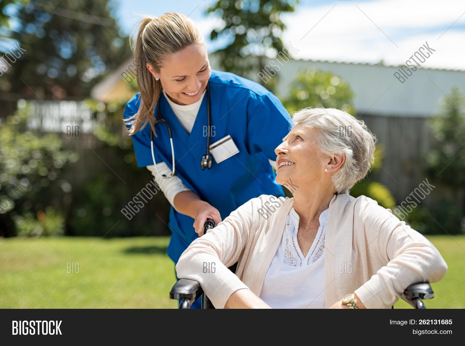 Nurse taking care of old woman in wheelchair outdoor. Friendly doctor caring about elderly disabled