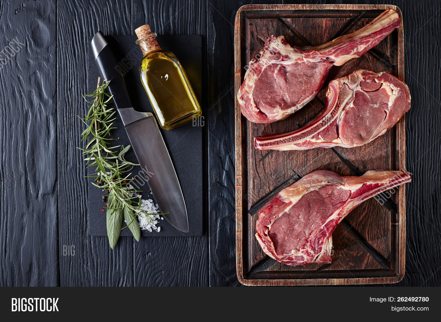 three Dry aged raw tomahawk or cowboy beef steaks on an old rude wooden cutting board on a black table with knife, spice and herbs, close-up, flat lay, view from above