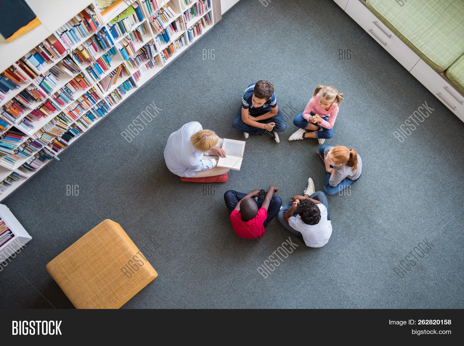 book,boy,boys,child,childhood,circle,class,classroom,cute,diversity,education,elementary,elementary school,elementary students,ethnicity,fairy tale,floor,girl,girls,group,growth,happy,high angle view,kid,knowledge,learning,librarian,library,listen,multi ethnic group,multiethnic,nursery,preschool,primary,read,school,sitting,sitting in circle,sitting on floor,story,teacher,teacher and student,teacher reading to students,top,top view,view,woman,young