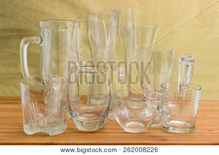 Different empty beer glassware, wine glasses, glass beakers and cups on a bamboo wooden surface stock photo