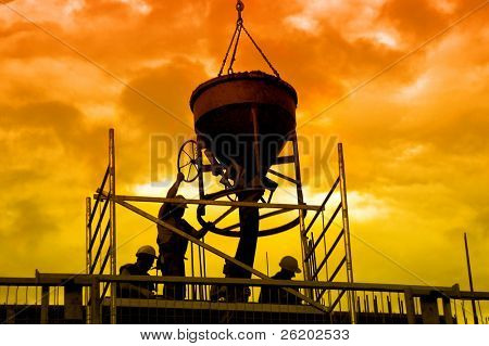 Silhouettes of construction workers pouring concrete mix at the building site over sunset sky stock photo