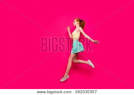 Full body length size, profile side view of nice adorable charming positive dreamy red-haired girl in tanktop and short skirt with ponytail, running in air, isolated on bright vivid fuchsia background stock photo