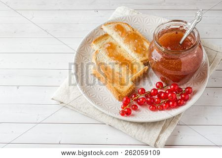 Healthy Breakfast with toast, jam and red currants on the white stock photo