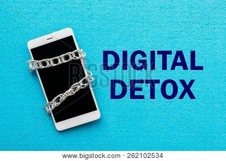 White smartphone with metal chain on blue background. Digital detox, dependency on tech, no gadget and devices concept stock photo