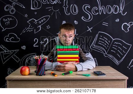 Puzzled youngster sitting at the desk with a pile of books under the chin, surrounded with school supplies. Chalkboard as a background stock photo