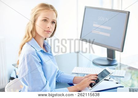 Shot of young businesswoman using her cell phone and text messaging while sitting at office desk in front of computer, stock photo