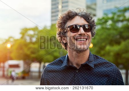 Portrait of smiling man wearing sunglasses and looking away in the city streets. Cheerful mature bus