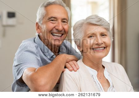 Portrait of happy healthy senior couple at home. Romantic old couple sitting together on sofa while