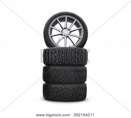 Four new good-looking snow tires isolated on the white background. A set of studded winter car tires. A set of wheels and tyre packages. Wheel parts stock photo