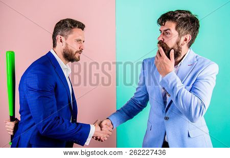 Businessman hides bat behind back while shaking hands. Hidden threat concept. Business partners competitors office colleagues shaking hands. Tricky first impression. Hidden danger. Fell into trap stock photo