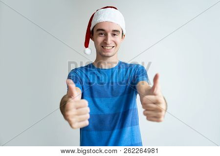 Happy man wearing Santa hat and showing both thumbs up. Handsome guy advertising something and looking at camera. Christmas offer concept. Isolated front view on white background. stock photo