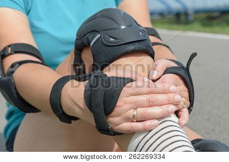 Woman rollerskater putting on knee protector pads on her leg and wearing wrist guards  stock photo