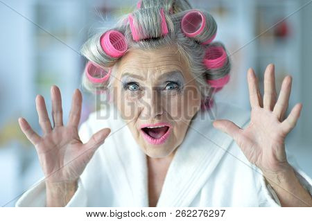 Portrait of a senior woman in bathrobe with curlers stock photo