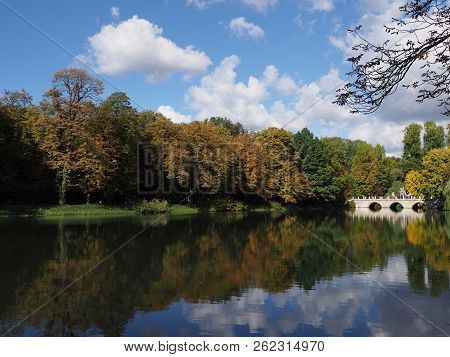 Picturesque white bridge in baths park landscapes in Warsaw, european capital city of Poland with cloudy blue sky in 2018 warm sunny autumn day on September stock photo
