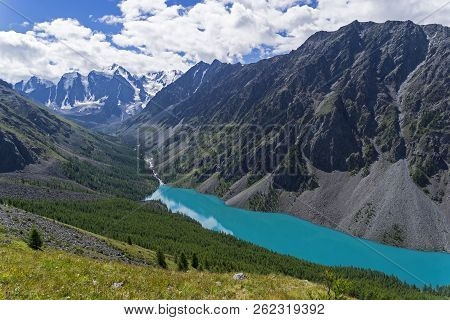 Aerial view of the Lower Shavlinskoe Lake. August. At the end of the valley of the river Shavla, you can see three peaks of the North-Chuisky ridge: Dream, Fairy Tale and Beauty (Mechta, Skazka and Krasavitsa). Altai Mountains, Siberia, Russia. stock photo
