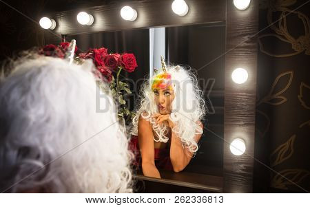 Freaky young woman in unusual wig looks at himself in the mirror in dressing room. Portrait of strange lady in red dress. Funny girl unicorn makes faces. stock photo