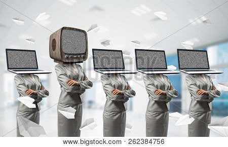 Business women in suits with laptops instead of their heads keeping arms crossed while standing in a row and one at the head with old TV inside office building. stock photo