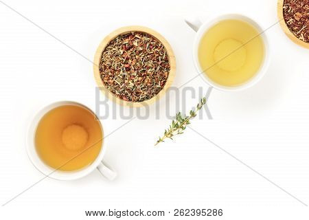 An overhead photo of tea, two cups and two bowls with loose dried tea leaves, on a white background with a thyme branch and copy space stock photo