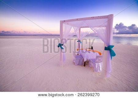 Romantic dinner setting on the beach at sunset. Couple or honeymoon concept. Copy space. stock photo