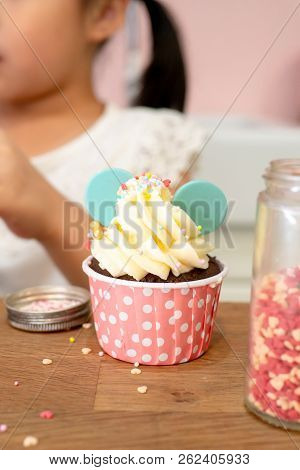 Children (kid) make (cooking) cute choclate cupcake decoration with sugar decorating. stock photo
