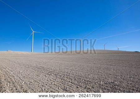 landscape of dry winter field with wind power turbines in horizon near to Ampudia town, in Palencia Spain stock photo