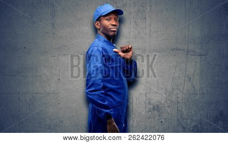 African black plumber man proud, excited and arrogant, pointing with victory face stock photo