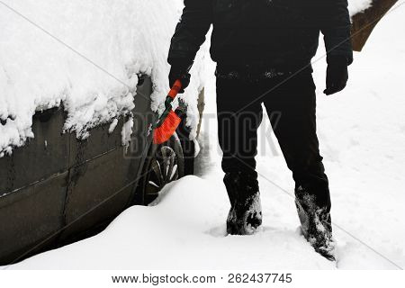Winter. Machine, covered with snow. A man cleans snow with a brush from the car. stock photo