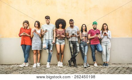Multiracial Friends Using Smartphone Against Wall At University College Backyard - Young People Addi