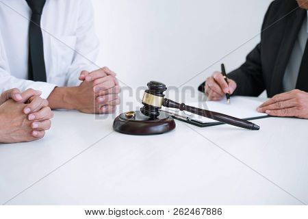 Agreement prepared by lawyer signing decree of divorce (dissolution or cancellation) of marriage, husband and wife during divorce process with male lawyer or counselor and signing of divorce contract. stock photo