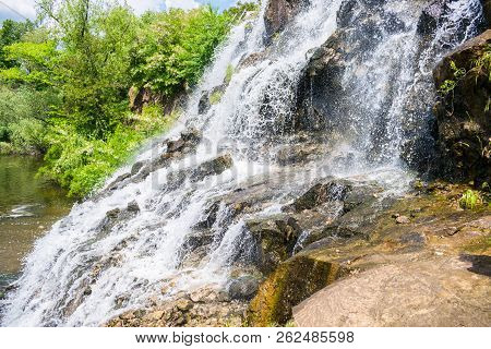 A large waterfall in a wild forest. Water falls from high rocks. Stones, river and wild nature. Beautiful background stock photo