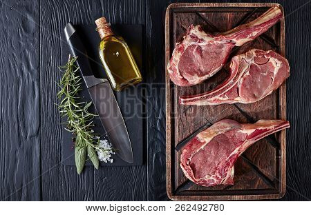 three Dry aged raw tomahawk or cowboy beef steaks on an old rude wooden cutting board on a black table with knife, spice and herbs, close-up, flat lay, view from above stock photo