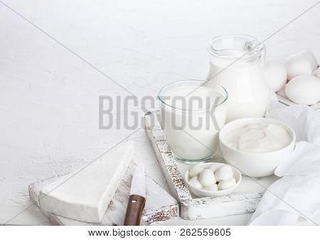 Fresh dairy products in vintage wooden box on white table background. Jar and glass of milk, bowl of sour cream and cheese. stock photo